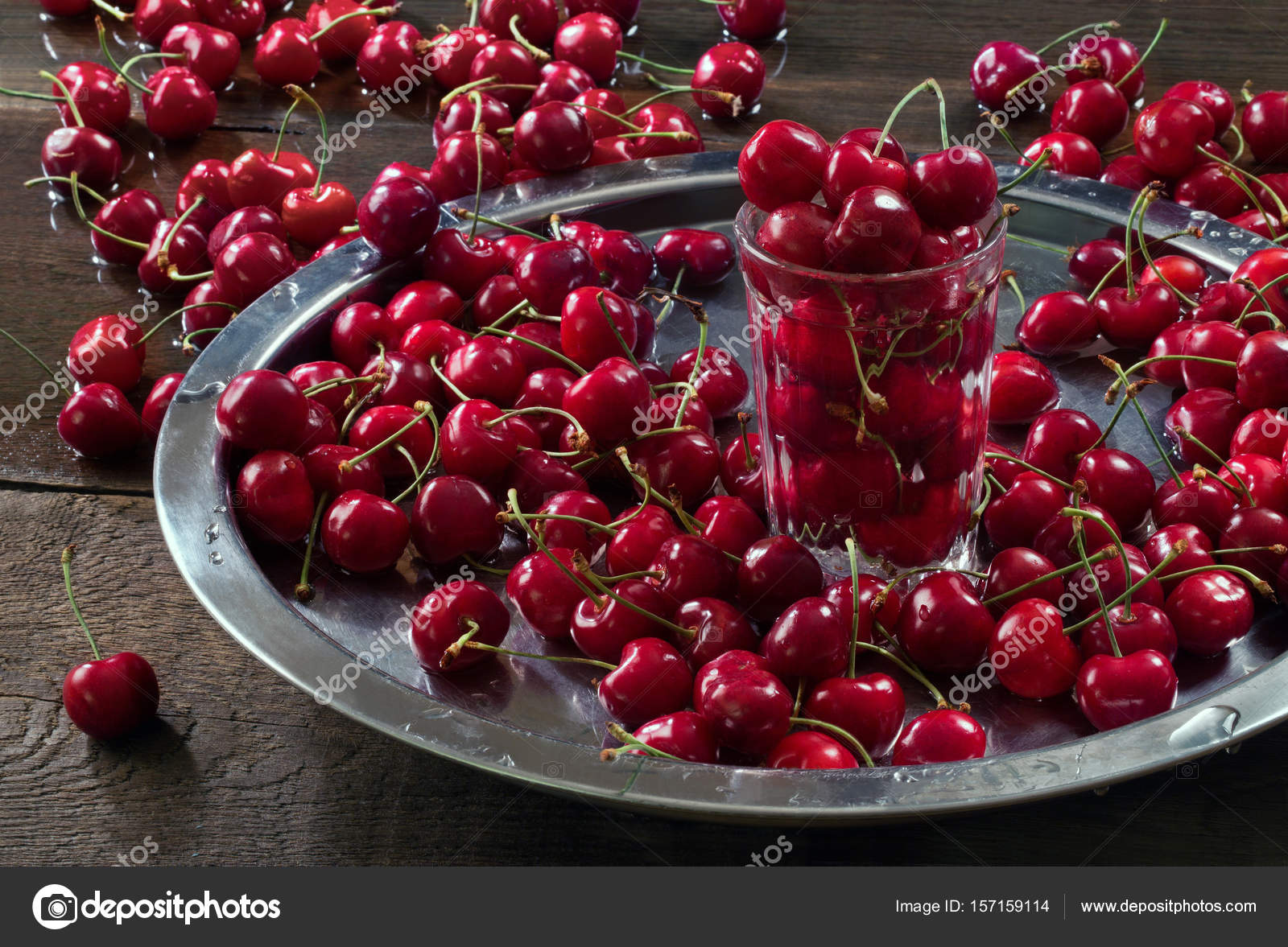 A lot of cherries on the table, on a tray and in a glass